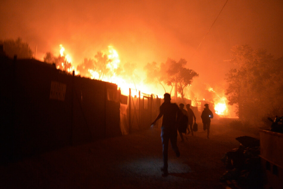 Refugees run while a fire burns in the refugee camp Moria on the island of Lesbos.