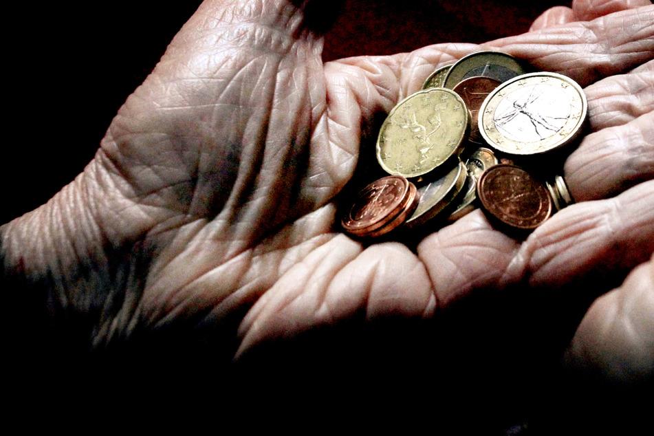 Eine alte Frau hält verschiedene Münzen – würde das Rentenalter erhöht, so droht eine Verschärfung der Altersarmut.