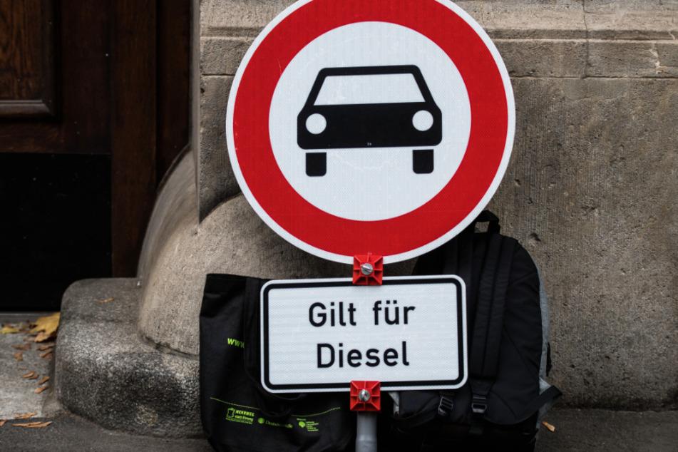 """Ein Verkehrsschild """"Verbot für Kraftfahrzeuge"""" mit dem Zusatz """"Gilt für Diesel"""" steht vor einem Gericht."""