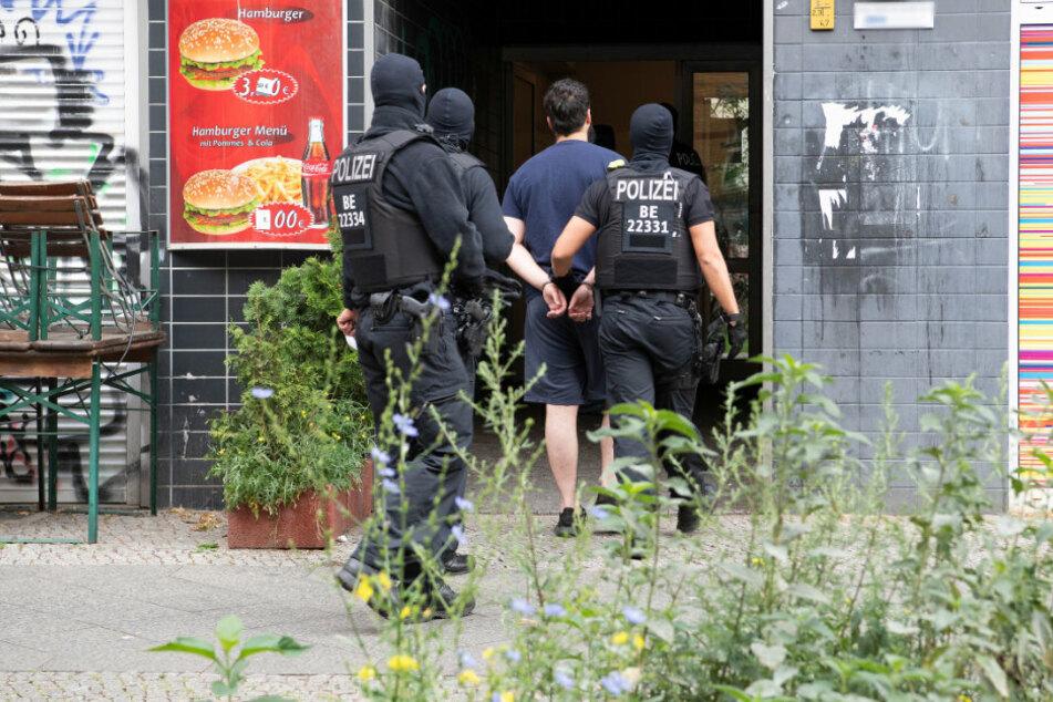 Polizeibeamte führen einen mit Handschellen gefesselten Mann in ein Haus in Berlin-Kreuzberg im Rahmen einer groß angelegten Razzia gegen Tatverdächtige aus der islamistischen Szene in verschiedenen Berliner Ortsteilen.