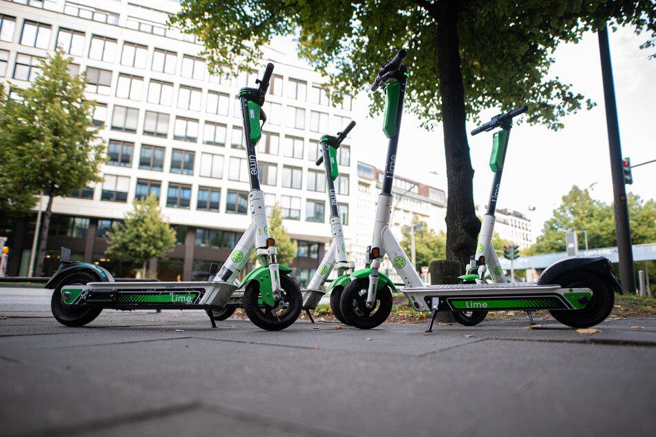 Roller des Elektro-Scooter-Anbieters Lime stehen auf einem Gehweg in Hamburg.