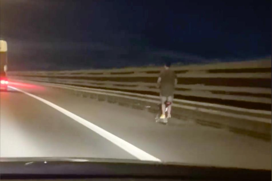 Ein unbekannter Mann fährt mit einem E-Scooter auf dem Autobahn-Standstreifen nahe der belgischen Hauptstadt Brüssel.