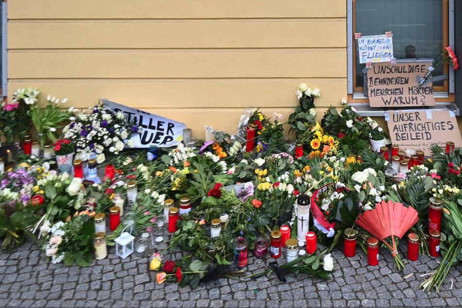 Blumen, Kerzen und Plakate liegen vor dem Eingang zum Wohnheim des diakonischen Anbieters Oberlinhaus. Am Donnerstag gedenken die Stadt Potsdam und die Einrichtung mit einem Gottesdienst der Opfer der Gewalttat vom vergangenen Mittwoch.