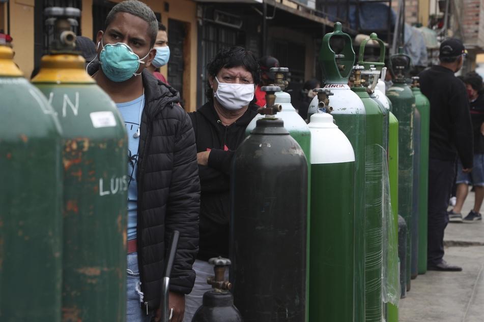 Menschen, die Mundschutz tragen, um die Ausbreitung des neuen Coronavirus zu verhindern, stehen Schlange, um ihre leeren Sauerstoffflaschen in Callao wieder aufzufüllen.