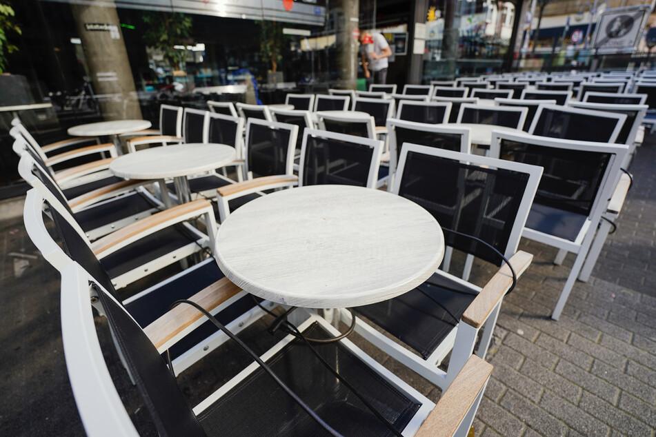 Leere Tische stehen vor einem Restaurant in Mannheim.