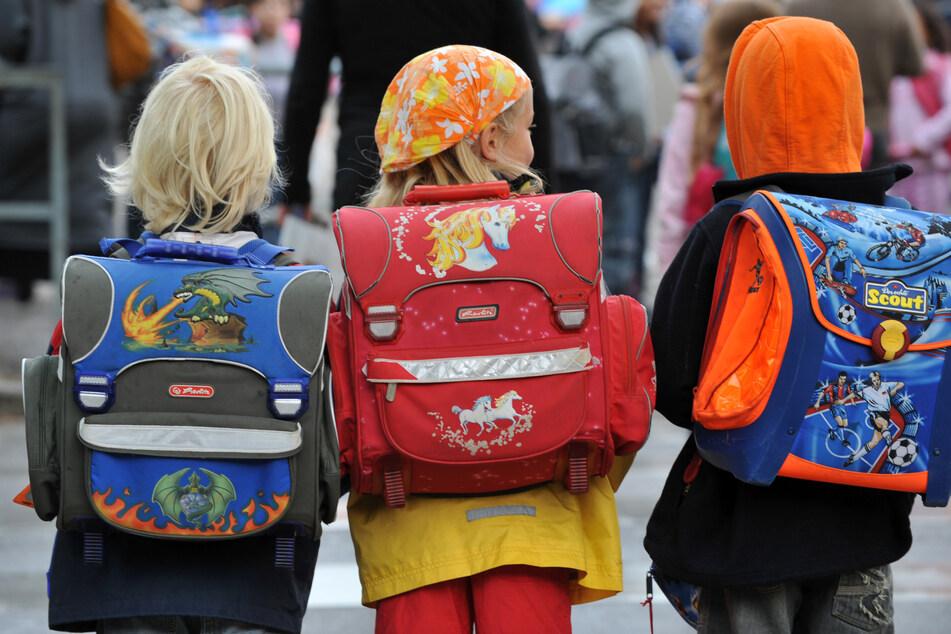Drei Kinder auf dem Weg zur Schule. Trotz rasant steigender Corona-Zahlen unter Schulkindern plant die Landesregierung keine schärferen Schutzmaßnahmen.