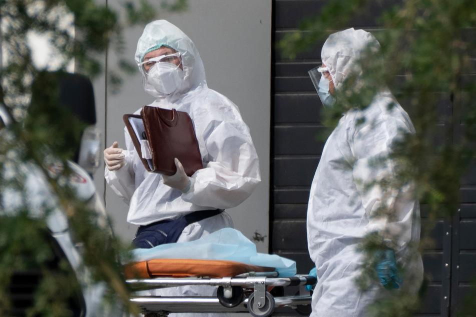 Medizinische Mitarbeiter in Schutzkleidung unterhalten sich, während sie einen Patienten mit Verdacht auf eine Coronavirus-Erkrankung in ein Krankenhaus transportieren.