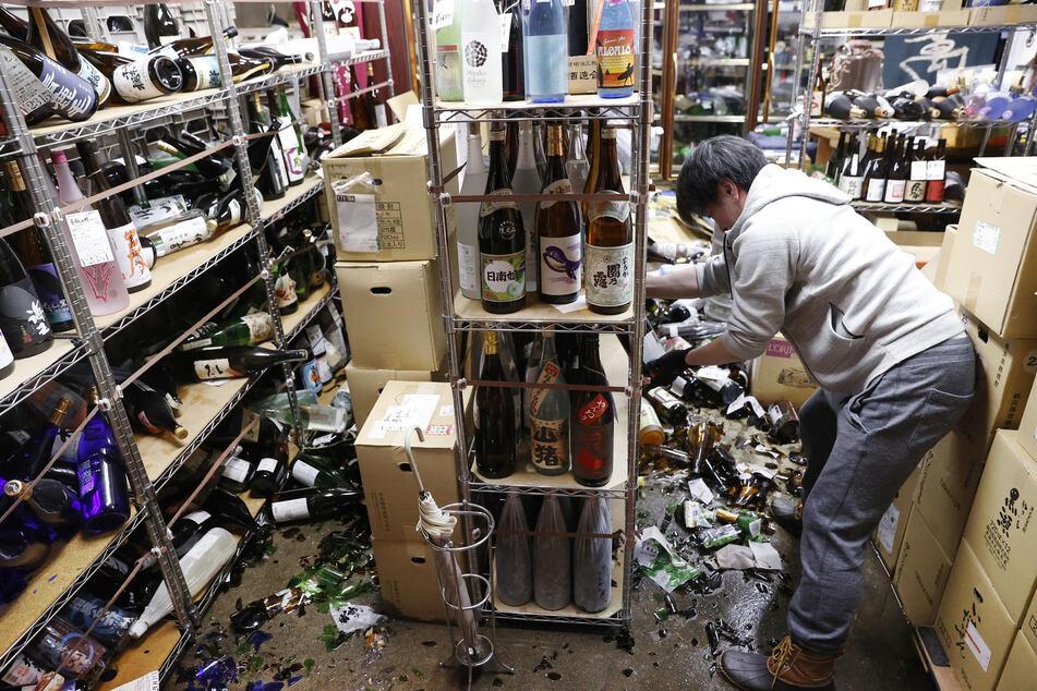 Der Inhaber eines Spirituosengeschäfts in Fukushima räumt nach einem starken Erdbeben in seinem Geschäft auf.