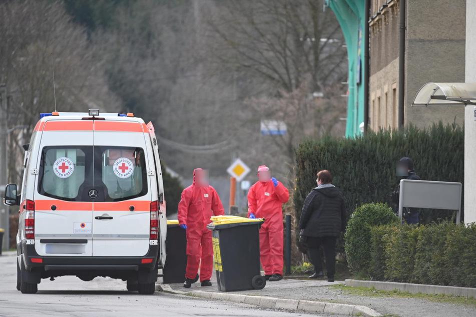 Mitarbeiter vom Deutschen Roten Kreuz holen betroffene Bewohner ab.