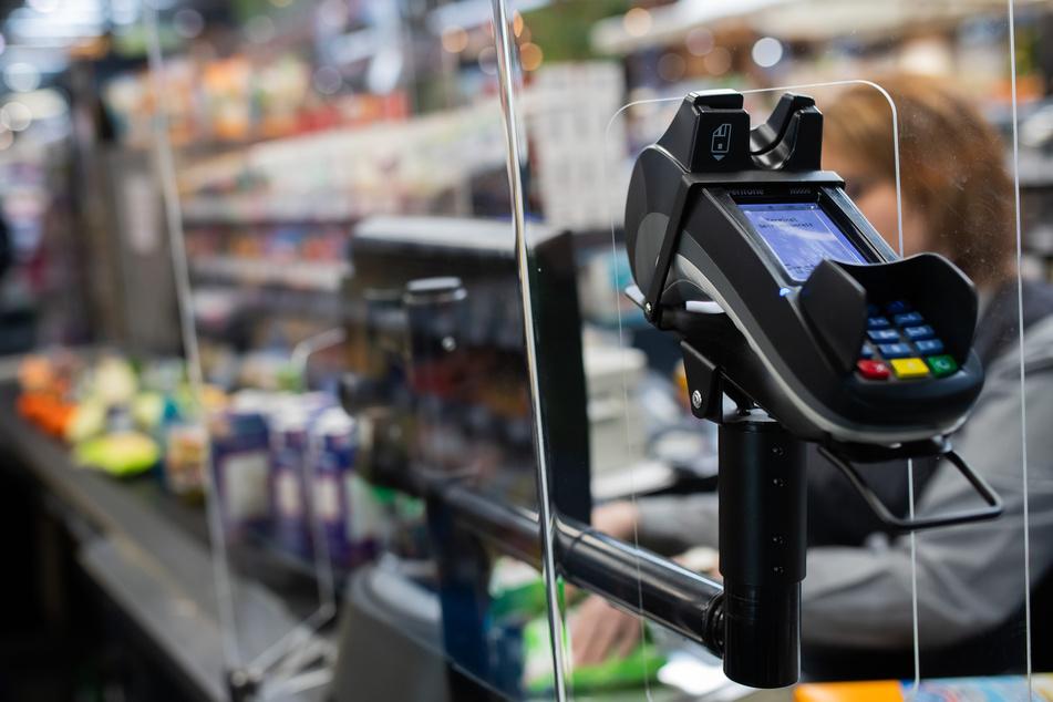 Eine Supermarktkasse wird durch ein Glasfenster geschützt.