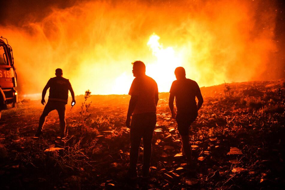 Feuerwehrleute und Dorfbewohner versuchen, ein Feuer in der Provinz Antalya unter Kontrolle zu bringen.