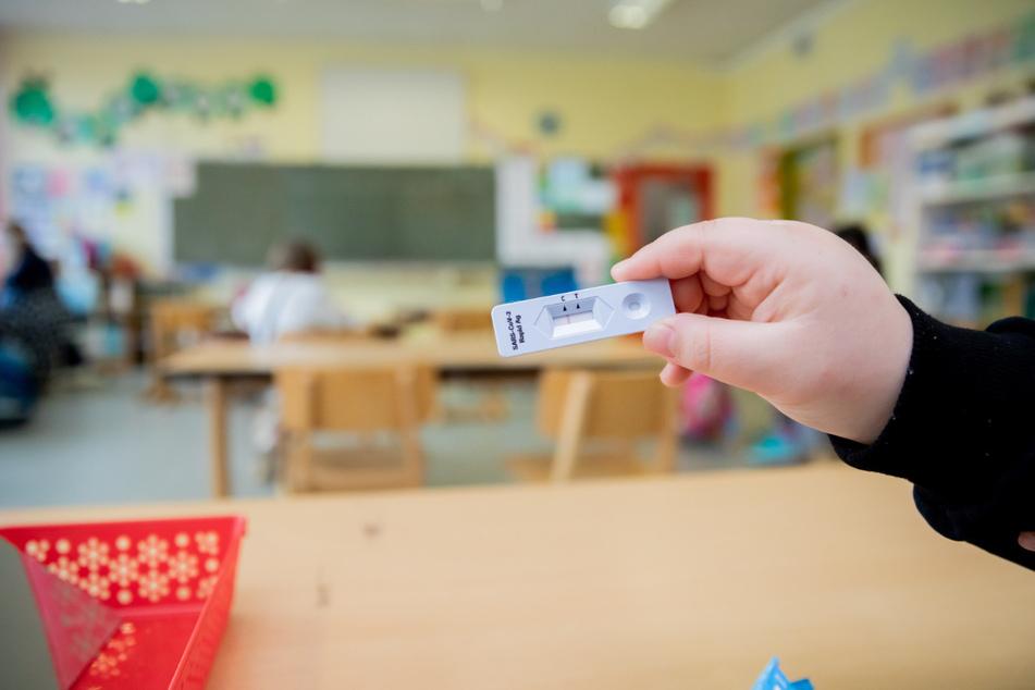 Ein Schüler hält bei einem Probelauf mit Corona-Schnelltests an der Grundschule in der Köllnischen Heide in Berlin-Neukölln seinen negativen Test in die Kamera.