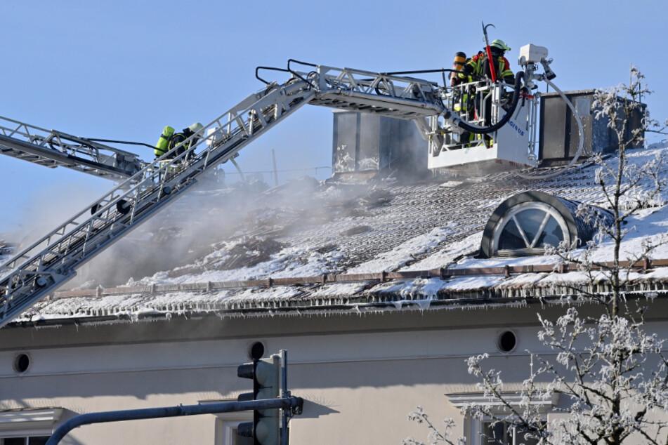 Feuerwehrleute auf Drehstühlen suchen im Dachstuhl des Rathauses von Sauerlach nach Glutnestern.
