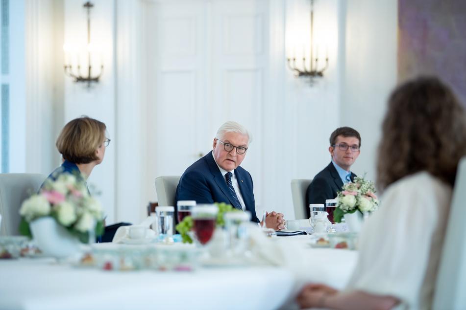Bundespräsident Frank-Walter Steinmeier (M) und seine Frau Elke Büdenbender (l) sitzen zusammen mit den Teilnehmern einer Kaffeetafel im Schloss Bellevue.