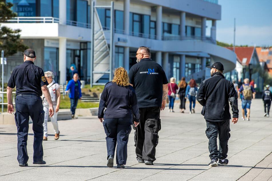 Mitarbeiter des Ordnungsamtes und einer privaten Sicherheitsfirma sind auf der Warnemünder Strandpromenade unterwegs.