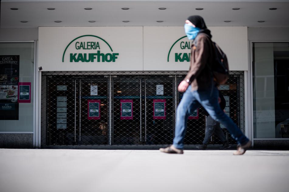 Ein Mann geht mit einem Schlauchschal, den er zum Schutz über Mund und Nase gezogen hat, am Eingang der Filiale der Kaufhauskette Kaufhof vorbei.