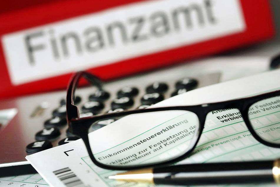 Auf einem Vordruck für die Steuererklärung liegt vor dem Aktenordner mit dem Aufdruck «Finanzamt» ein Stift und eine Brille.