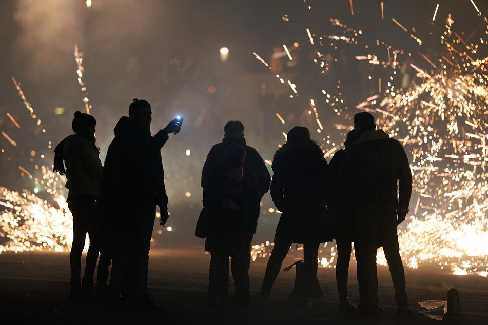 Eine Gruppe junger Menschen entzündet Feuerwerksraketen. (Symbolbild)