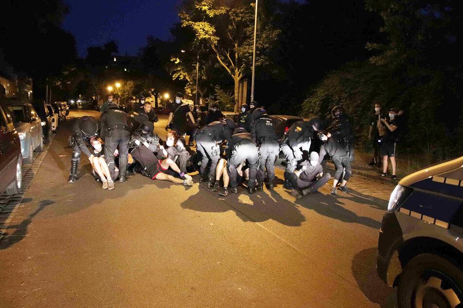 Als die drei Besetzer auf ein Polizeirevier gebracht werden sollten, blockierten rund 50 Personen die Straße. Polizisten mussten sie teils wegtragen.