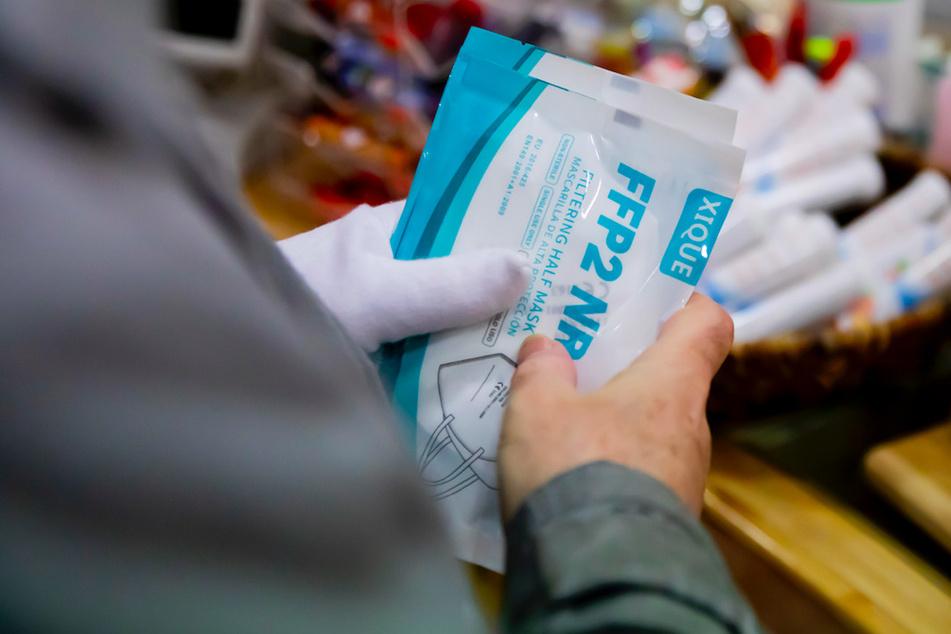 Ein Kunde hält in einer Apotheke FFP2-Masken, welche er im Rahmen der kostenlosen Ausgabe an Risikogruppen erhalten hat.