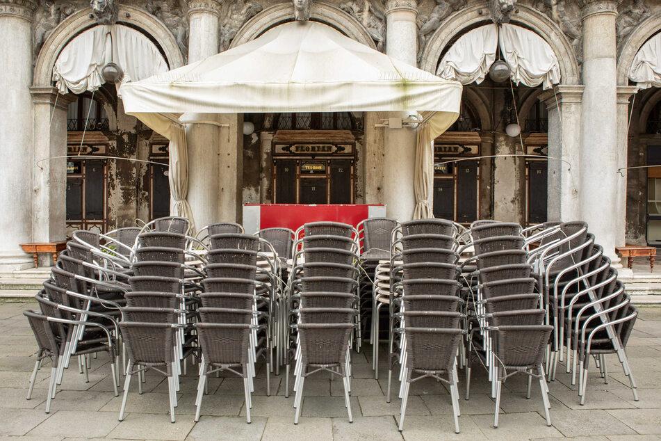 Stühle stehen gestapelt und zusammengestellt im Außenbereich eines geschlossenen Cafes.
