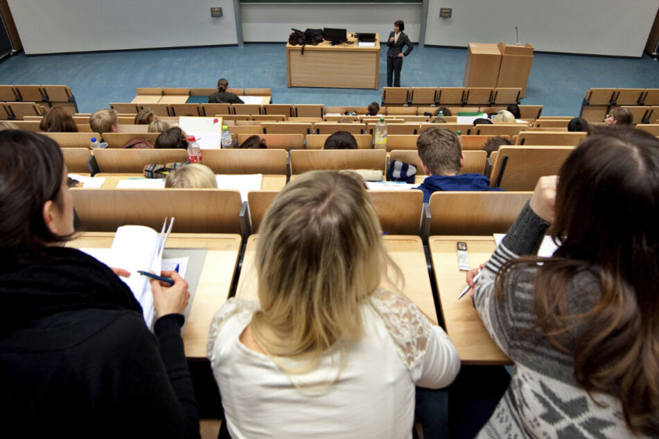 Studenten sitzen in einem Hörsaal und verfolgen eine Vorlesung.