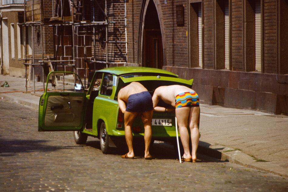 Zwei Männer in Badehose beugen sich in den Kofferraum eines grünen Trabant. Der Zweitakter war so begehrt, dass er noch nach Jahren der Nutzung zum Neupreis verkauft werden konnte.
