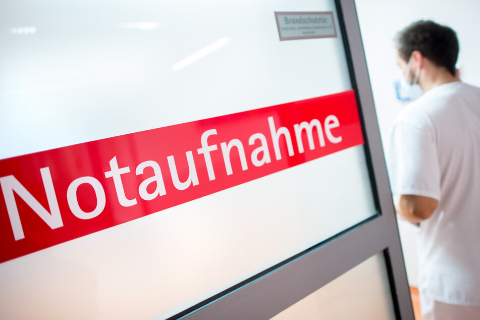 """Ein Krankenpfleger in einem Krankenhaus geht durch eine Glastür mit der Aufschrift """"Notaufnahme"""". Derzeit gibt es bei der Sieben-Tage-Inzidenz in Deutschland wenig Dynamik."""