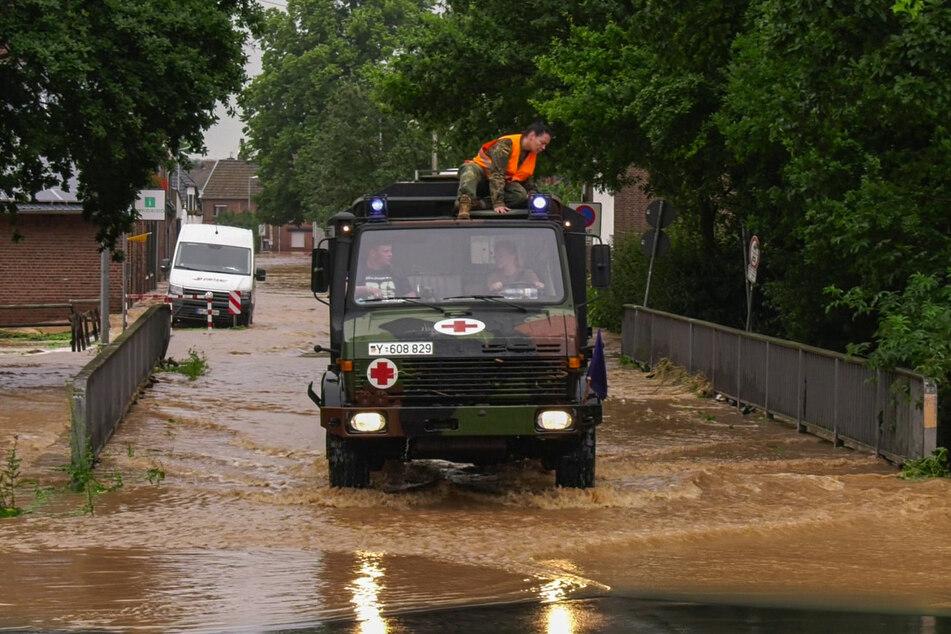 In Erftstadt fährt ein Fahrzeug der Bundeswehr durch eine überflutete Straße. Das Regen-Unwetter in NRW hat auf zahlreichen Autobahnen für überflutete Fahrbahnen gesorgt.