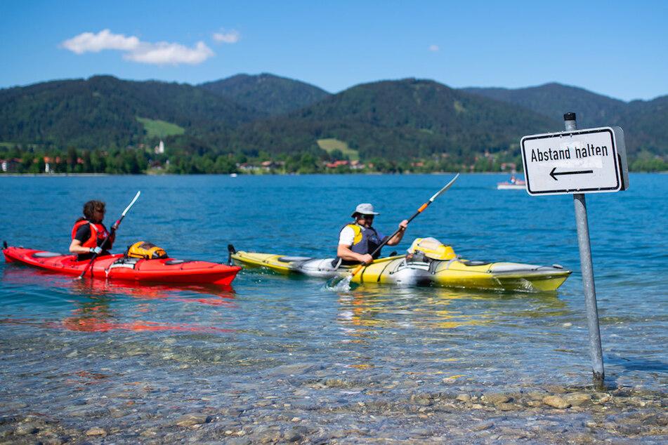 """Kajakfahrer paddeln auf dem Tegernsee an einem Schild mit der Aufschrift """"Abstand halten"""" vorbei."""