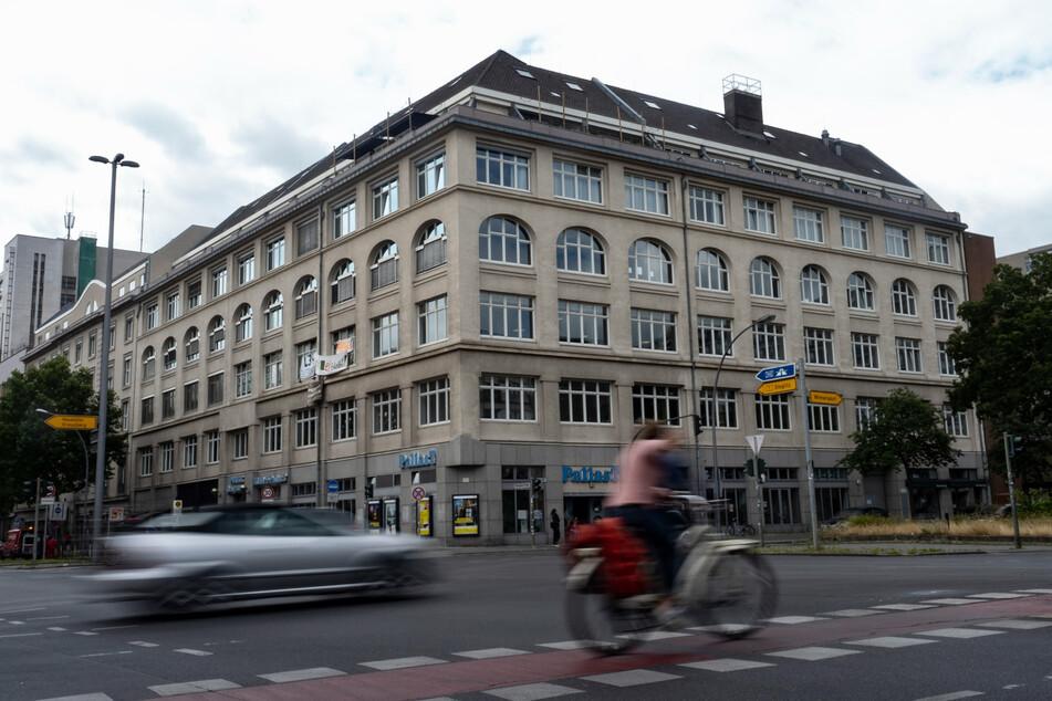 """Ein Pkw und eine Radfahrerin fahren an dem Haus vorbei, in dem das links-alternative Jugendzentrum """"Potse"""" in Schöneberg untergebracht ist."""
