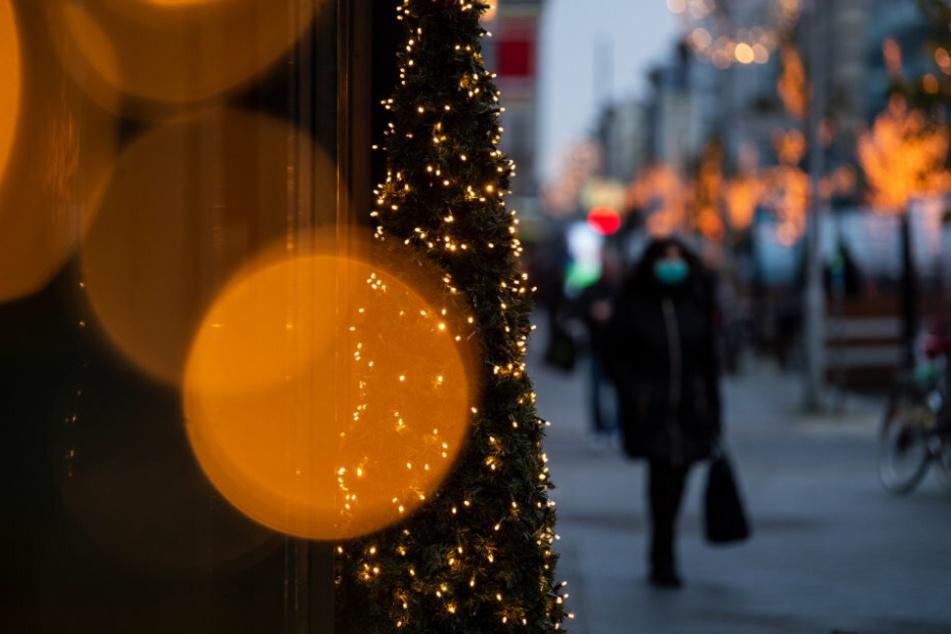 Auf der weihnachtlich geschmückten Friedrichstraße in Berlin laufen Personen