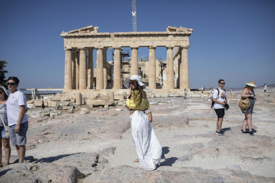 Touristen spazieren über die Athener Akropolis und machen Fotos vor dem Parthenon.