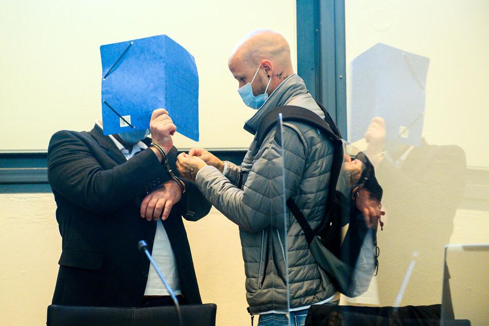 Der Angeklagte (l.) steht in einen Saal des Landgerichts in Magdeburg und verdeckt sein Gesicht mit einem Ordner, während ihm ein Mitarbeiter der Justiz die Handschellen abnimmt.
