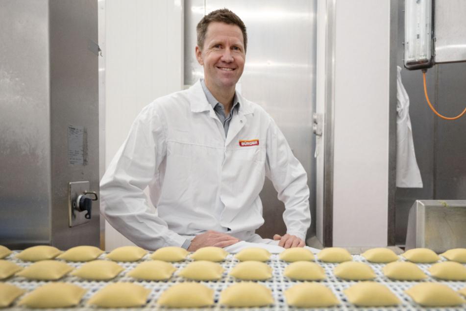 Martin Bihlmaier, Geschäftsführer des Teigwarenproduzenten Bürger GmbH & Co. KG, sitzt hinter einem Band, auf dem Maultaschen liegen.