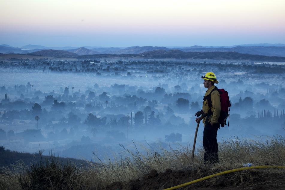 Ein Feuerwehrmann blickt auf ein niedergebranntes Gebiet.