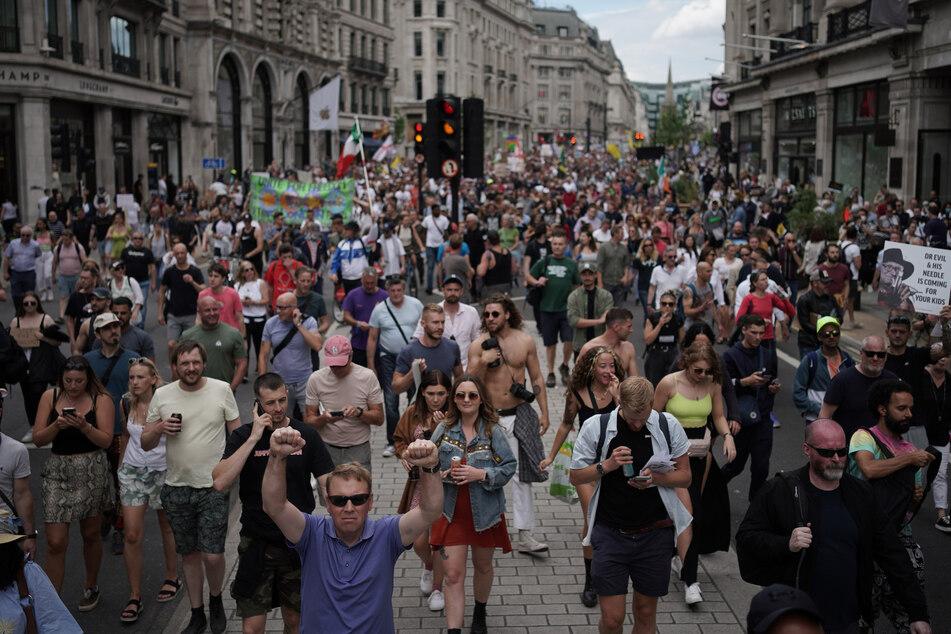 Demonstranten gehen am Samstag bei einem Protest für ein Ende der Maßnahmen zur Eindämmung der Corona-Pandemie und des Lockdowns die Regents Street entlang.