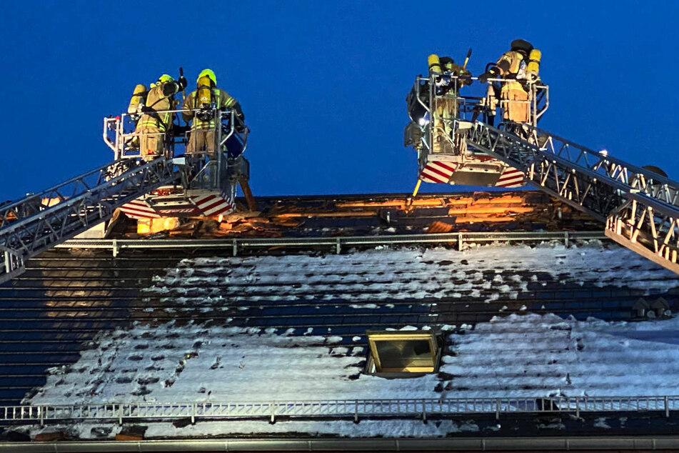 Die Einsatzkräfte nähern sich über Drehleitern dem Brandherd unter dem Dach.