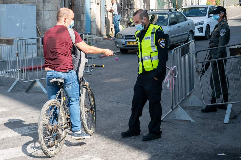 Ein Polizist (r) lässt sich von einem Radfahrer den Ausweis zeigen.