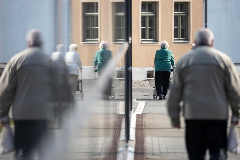 Ältere Menschen machen trotz der Situation um das Coronavirus in der Sonne einen Spaziergang. (Symbolbild)