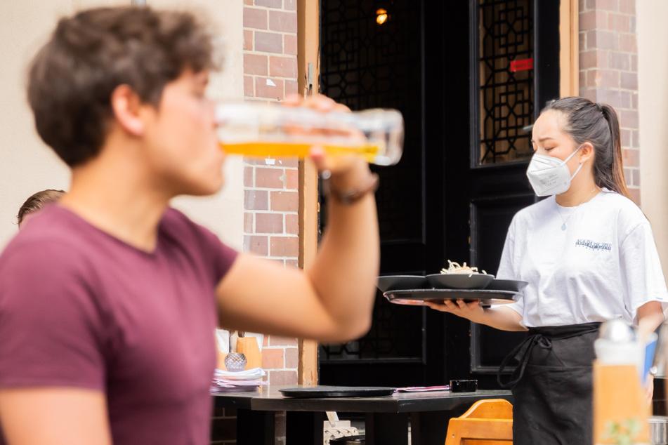 Eine Kellnerin, trägt im Berliner Bezirk Prenzlauer Berg in einem Restaurant für asiatische Fusionsküche ein Tablett.
