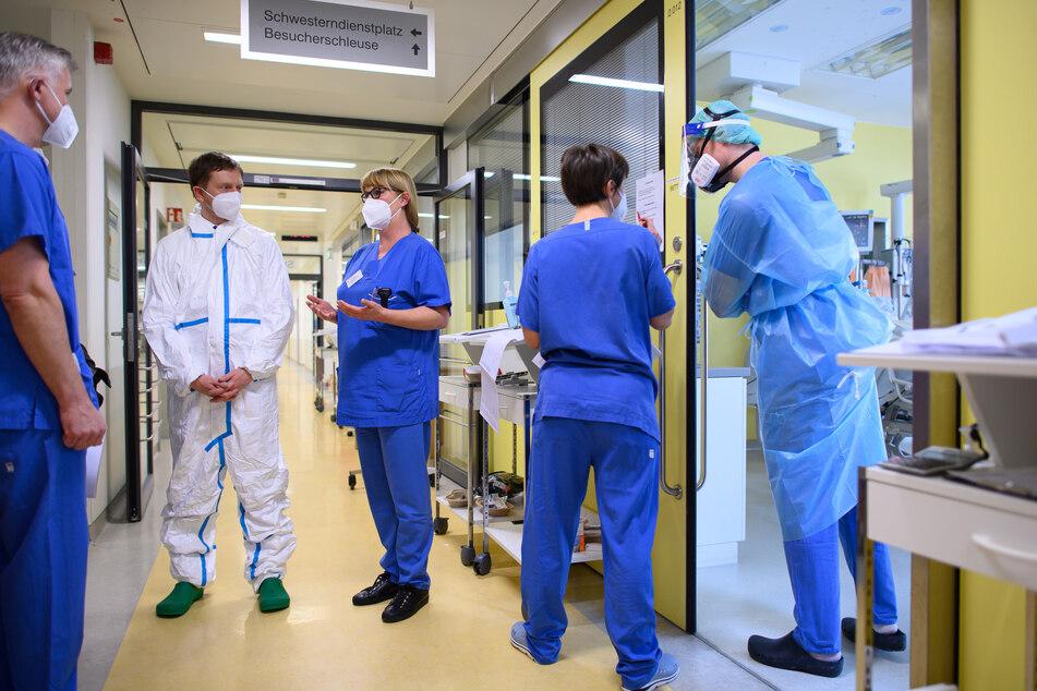Michael Kretschmer (CDU, 2.v.l.), Ministerpräsident von Sachsen, steht im Vollschutzanzug auf der Covid-19 Intensivstation im Städtischen Klinikum Dresden.