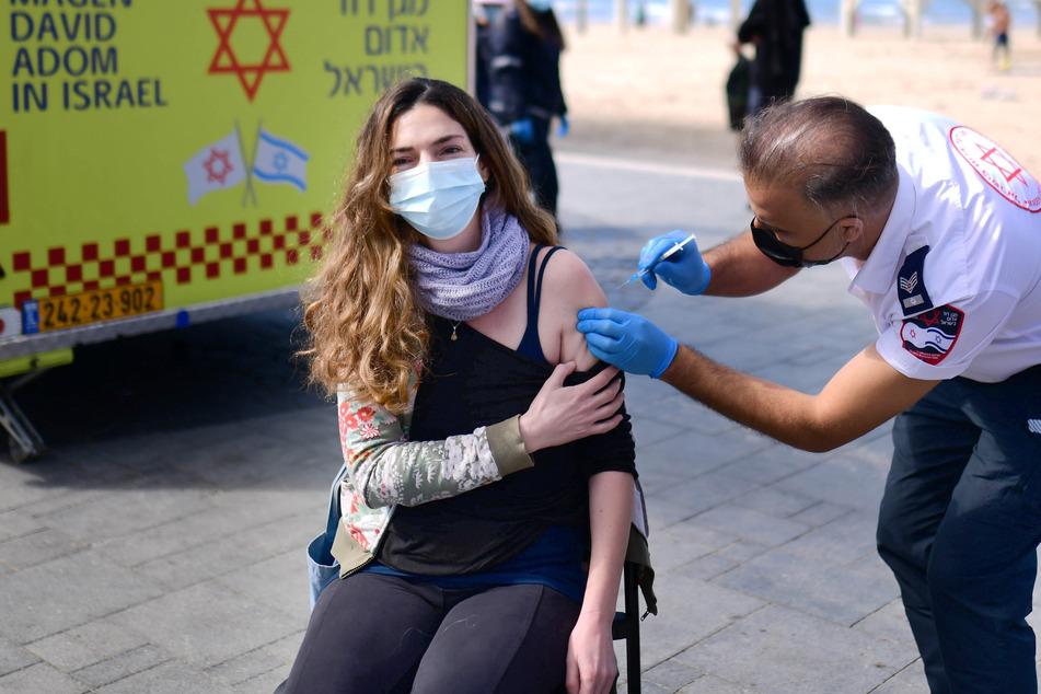 Eine israelische Frau wird in einer provisorischen Einrichtung in Tel Aviv des israelischen Rettungsdienstes Magen David Adom gegen das Coronavirus geimpft. Fast 62 Prozent der 9,3 Millionen Landesbewohner haben bereits eine erste Corona-Impfung erhalten, fast 56 Prozent auch die zweite Dosis.