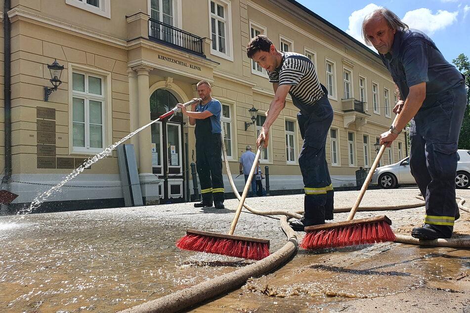 Feuerwehrleute beseitigen vor der Kirnitzschtal-Klinik Bad Schandau Schlamm und Dreck.