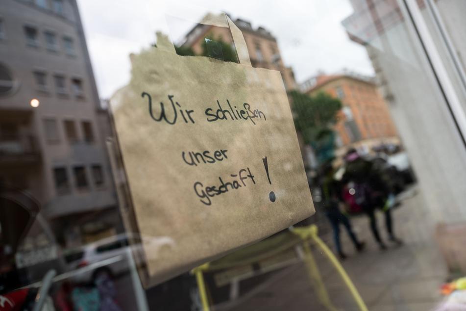 """Eine Papiertasche mit der Aufschrift """"Wir schließen unser Geschäft"""" hängt an einem Einzelhandelsgeschäft in der Stuttgarter Innenstadt."""