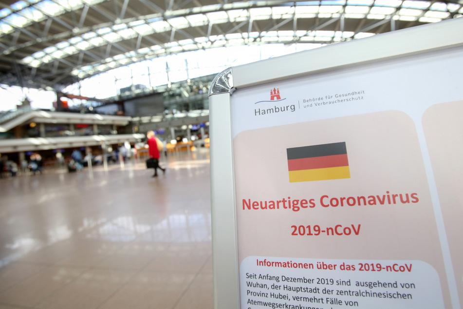 Auf einem Aussteller der Gesundheitsbehörde und des Robert Koch Instituts wird am Flughafen Hamburg auf Verhaltensweisen in Bezug auf das neuartige Corona-Virus hingewiesen.
