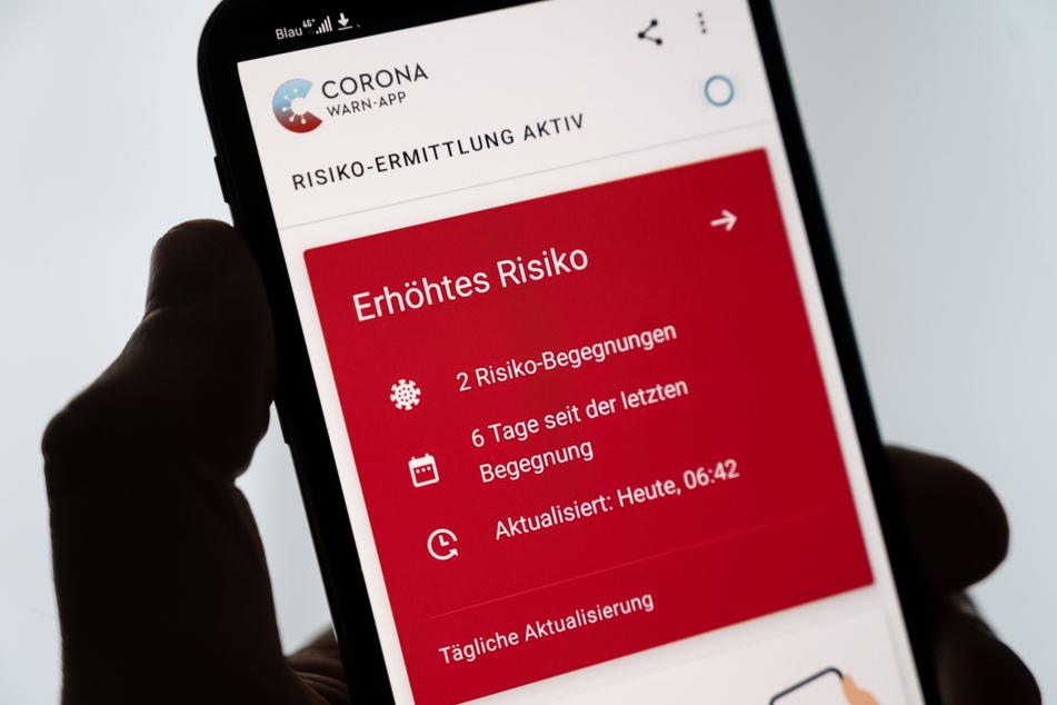 Ein Mann hält ein Smartphone in der Hand, auf dem die Corona-Warn-App der Bundesregierung ein erhöhtes Risiko anzeigt.