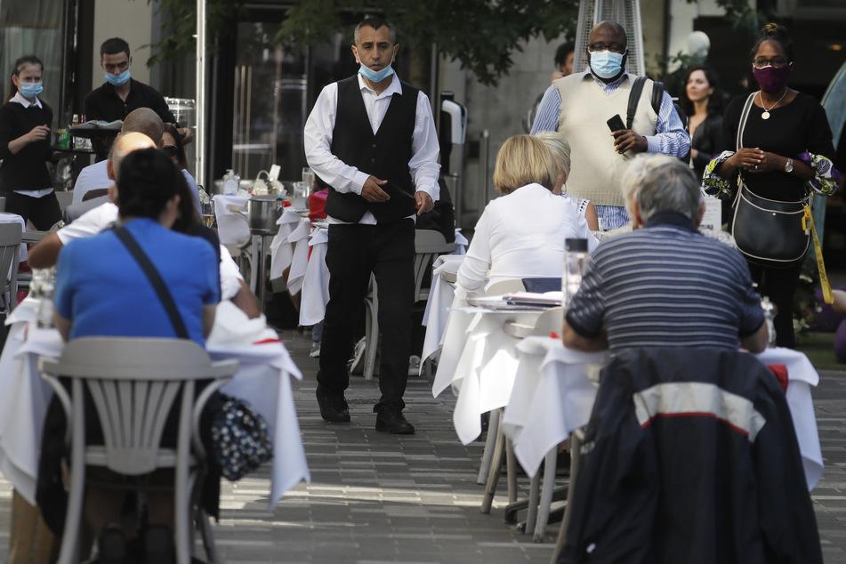 """don: Menschen essen in einem Restaurant. Angesichts eines rapiden Anstiegs von Corona-Fällen steht Großbritannien laut Gesundheitsminister Hancock an einem """"Wendepunkt""""."""