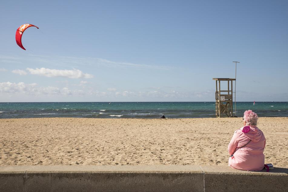 Eine deutsche Touristin sieht ihrem Sohn beim Kitesurfen an einem stürmischen Tag an der Promenade Playa de Palma zu.