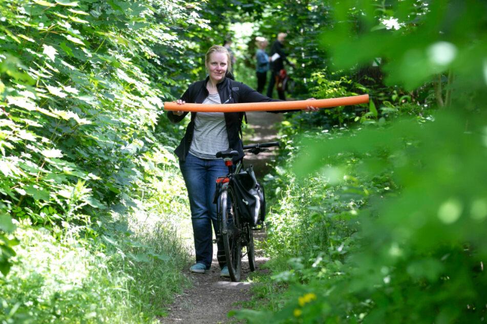 Stadtbezirksbeirätin Claudia Creutzburg (40, Grüne) zeigt, wie breit der Waldweg geschnitten werden muss.